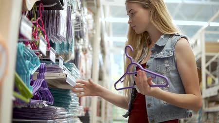 şey : Young blonde woman is taking plastic coat hangers in a sale in supermarket. She is rotating in hands, comparing and choosing different colors Stok Video