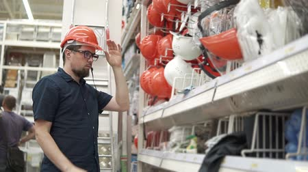 caixa de ferramentas : Male buyer choosing and trying on a building helmet in a building store. Man looking for building tools and equipment. Man shopping.
