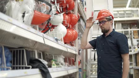 o : Bearded guy is choosing construction helmet in hypermarket for builders. He is standing in a hall in shop and trying on orange hat