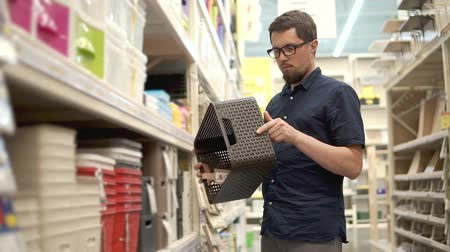 buyer : Bearded adult guy is twirling plastic container in hands, standing in a hall of shop. He is selecting basket for home, shopping in a hypermarket