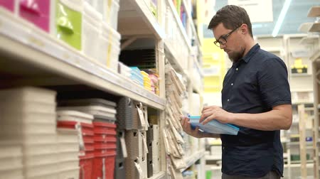 tutmak : Handsome man is examining plastic box in a store. He is opening cover and looking inside, thinking about buying