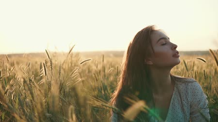 kasze : Young girl is sitting on meadow with ears of wheat in evening in summer. Beautiful sunset is behind her back