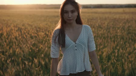contemplative : Pensive young woman is strolling alone in meadow in evening. She is looking at camera calmly, sun is setting in horizon behind her Stock Footage