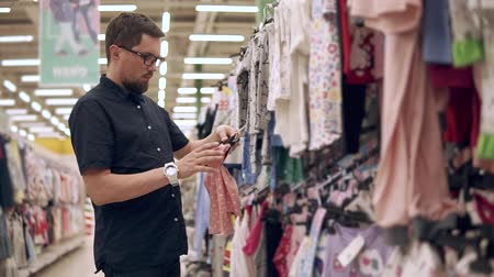 потреблять : Casual father choosing new dresses and outfits for his child, shopping alone. Man in glasses buying kids clothes in mall.
