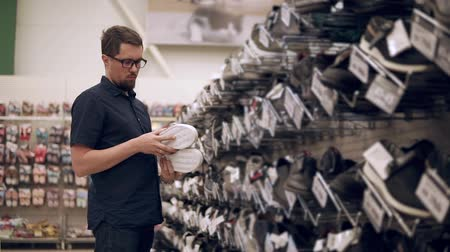 потреблять : Adult guy in glasses choosing new pair of everyday shoes, pair of nice stylish sneakers. Wide range of shoes in store, male customer shopping.