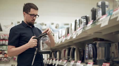 tek bir nesne : Householder is examining sample of electric tea kettle in a trading area in supermarket. He is looking on it, opening and closing cover