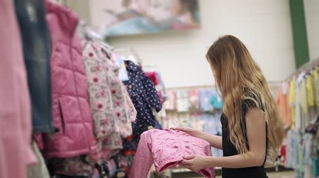 взял : Slim blonde woman is watching pink child jacket in a clothing store. She took thing from rack and checking quality and reading price tags Стоковые видеозаписи