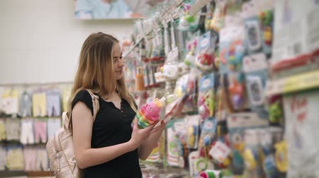 all ages : Portrait of a beautiful blonde mother buying toys for children at home, wide range of toys for kid of all ages. Woman shopping in toy department store.