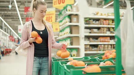 buyer : Young female customer choosing fresh ripe oranges in basket in grocery store. Choosing a citruses in a plastic net, healthy eating.
