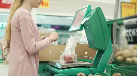 buyer : Young blonde woman is using electronic scale for weighing fruits in a shop of self service. She is pressing buttons and getting price tag for her goods