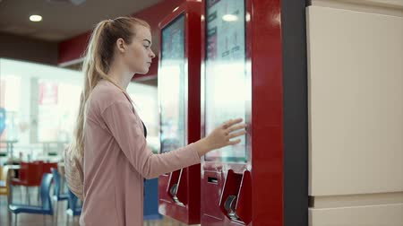 automaat : Female customer is using automat for ordering in fast-food cafe. Touching screen by hands, flipping up displays
