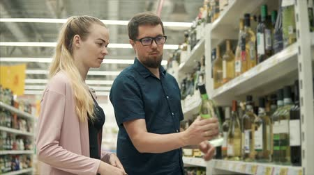kelder : Married pair is choosing wine in a shop. Man is taking bottles from shelf and reading labels, woman is talking with him