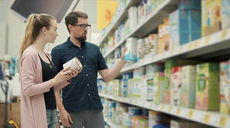 infant formula : Married couple is buying baby formula in supermarket. They are standing near shelf and taking different jars from it, reading ingredients Stock Footage