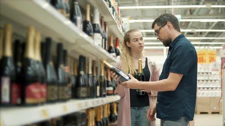 посетитель : Young girl and her husband are choosing champagne in a supermarket. Woman is holding two bottles and man is deciding what to buy Стоковые видеозаписи