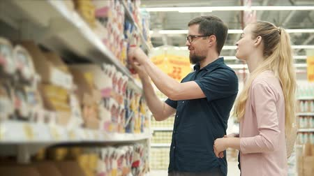 описание : Spouses are reading ingredients and description on packet with cat forage. They are standing in a hypermarket, man is holding package, woman is taking other