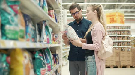grocery store : Couple standing in aisle with pet food and choosing big bag of dry dog food, pet is family. Customers picking best brand of dogs food. Stock Footage