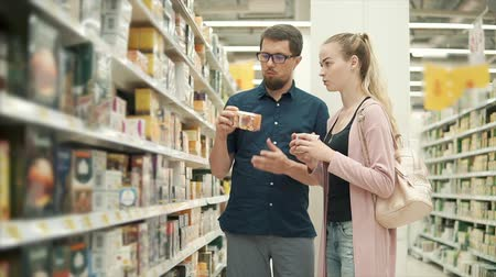 tea bag : Man and woman standing in the aisle with tea, difficult choice. Plenty tea boxes on shelf in supermarket, family couple shopping together.