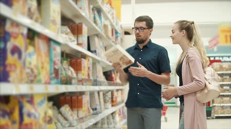 покупка товаров : Man and woman are debating a cereal for cooking in a grocery department of supermarket. Husband is offering product and woman is deciding