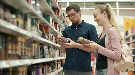 粒状 : Adult man and woman are standing in a department of supermarket, holding coffee jar on hands. They are examining ingredients and descriptions on labels