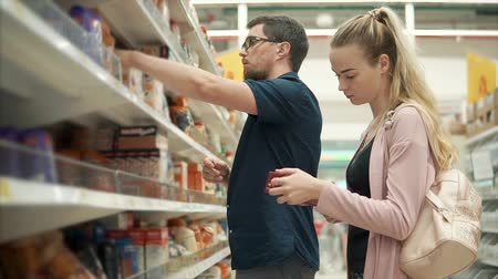 grocery : Couple buying food on weekends in supermarket. Family buying nutritional food for breakfast, different boxes of oatmeal and cereal.