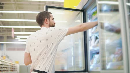 mrazák : Handsome man taking frozen food from shelves in a fridge of a grocery store. Man with a tattoo shopping for food, buying groceries in supermarket.