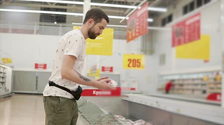 zamrażarka : Young casual guy picking fozen meat from a freezer, choosing food in supermarket. Wide range of frozen products in a freezer. Wideo