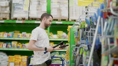 посетитель : Male customer of hypermarket is choosing tools in department. He is taking hatchet, spinning in hands and hanging back on shelf Стоковые видеозаписи