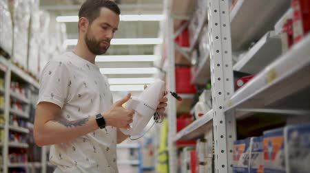 parník : Man chooses new manual vacuum cleaner in a hardware store, checking quality of appliance. Customer holding a white dustbaster, cleaning.