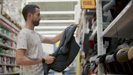 kayış : Young father is inspecting new child car seat in store. He is checking construction and quality of item, caring of new born Stok Video