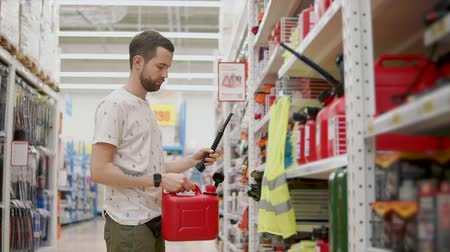 galão : Male shopper is examining red plastic can for liquid with nozzle for car in store. Driver is choosing tools for garage Vídeos