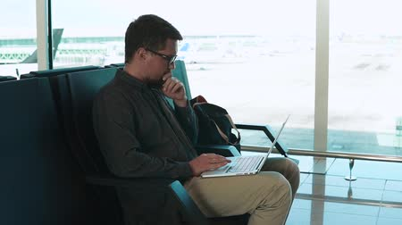 район : Man with beard and glasses is texting messages by keyboard of notebook. He is sitting alone in departure lounge of airport near big windows Стоковые видеозаписи