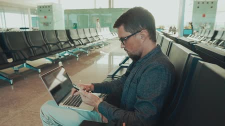 registration : Close-up shot of a male tourist using smartphone and laptop at airport terminal while waiting for flight. Airport wifi, sitting on internet.