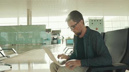 o : Young bearded man is sitting alone in a departure lounge and using laptop. He is watching on a display and typing text in sunny day