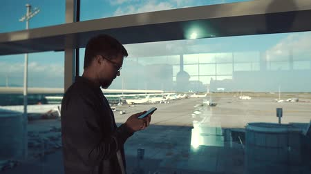registration : Adult man in eyeglasses using smartphone in airport standing by the big window, airport area. Man sitting online indoor, airport terminal zone.