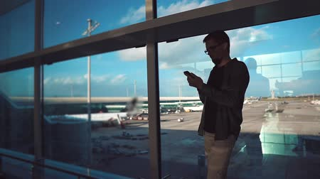 o : Alone man is browsing in internet by mobile phone, standing against huge windows in airport. He is using free wifi in departure hall, view in planes behind him