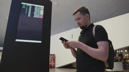 várjon : Portrait of a handsome man with backpack using smartphone by digital information board. Smiling man sms texting indoor.