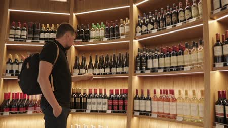 продуктовый : Adult man with a backpack choosing wine in a duty free in airport, buying alcohol. Wide range of diffrent kinds of alcohol, before the flight.