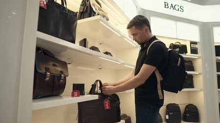 supermarket shelf : Male shopper is inspecting leather bag on a sale in a store. He is touching surface of handbag and reading price tag Stock Footage