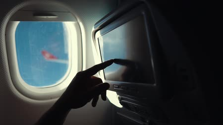 бортовой : Man is adjusting a display in a seat of plane, choosing music during flight. He is sitting near window with view on wing, close-up of hand Стоковые видеозаписи