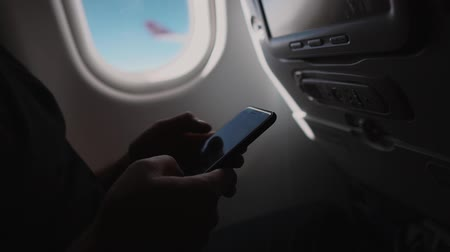 fülke : Male passenger is texting sms by mobile phone, close-up. He is sitting on a board of aircraft near window with view on wing Stock mozgókép