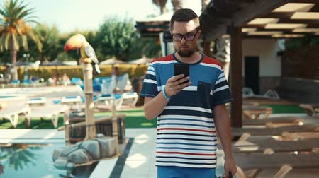 cuidadoso : Man with glasses is going out from pool area in hotel and spa in summer day. He is reading messages on display of his smartphone