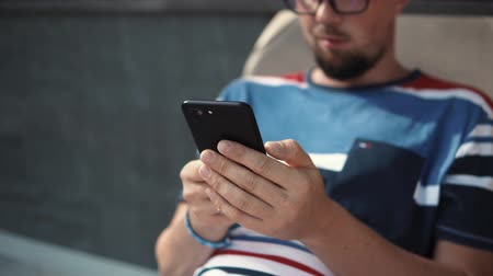 restful : Close-up shot of a smiling grown man texting sms on smartphone. Man chatting with friends online, lying in lounge chair outdoor under sun.