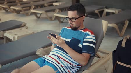 restful : Tourist in eyeglasses hanging out by the pool in a lounge chair, texting and chatting, sitting onlive from cellphone. Casual guy on a vacation.
