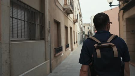 plano ciudad : Rear view of a adult male tourist with backpack exploring new city, nice walk in city, narrow streets. Man traveling on vacation, tourist season. Archivo de Video