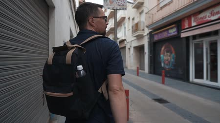 backpacken : Urban man walking around in the city, exploring new sightseeings, tourist season. Excited man strolling with backpack, narrow empty streets, looking around.
