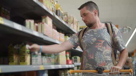 seçenekleri : Casual man choosing packet of juice in store, shopping for drinks. Man with backpack shopping in a supermarket, healthy juice. Stok Video