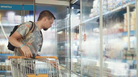 comparar : Casual guy with shopping cart choosing food in a grocery store. Man taking frozen yogurt out of freezer, tasty dessert.