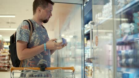 zamrażarka : Male customer taking ice-cream from a freezer in a grocery store, buying dessert for home. Shopping for food on weekends.