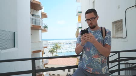 o : Man is standing on a balcony with view on port in summer day. He is surfing internet by mobile phone with wireless technology Stok Video