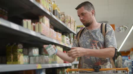 посетитель : Male visitor of food store is walking along rack with goods. He is rolling trolley, taking box from shelf, reading inscriptions and standing back